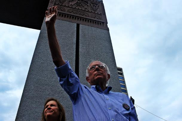 Bernie waves at the disappointed crowd as wife Jane looks on